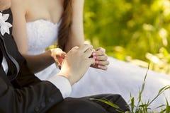 Au mariage, la jeune mariée mettant sur l'anneau sur le doigt du marié Photo stock