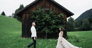 Au milieu des couples étonnants de champ se rencontrant dans l'avant d'une petite maison en bois banque de vidéos