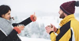 Au milieu du paysage étonnant avec la montagne et le touriste de la forêt deux obtenir chaud de boire une certaine boisson chaude banque de vidéos