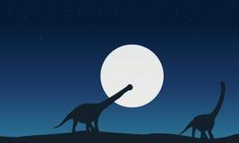 Au paysage d'argentinosaurus de nuit des silhouettes Photographie stock