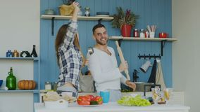 Au ralenti de jeunes couples joyeux ayez la danse d'amusement et le chant tout en faisant cuire dans la cuisine à la maison banque de vidéos