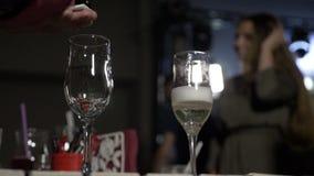 Au ralenti du champagne se renversant de serveur dans les verres pour la fille heureuse banque de vidéos