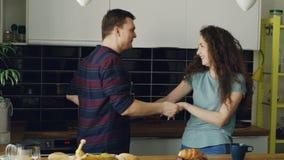 Au ralenti jeunes des couples gais et attrayants dans l'amour dansant ensemble la danse latine dans la cuisine à la maison dessus clips vidéos
