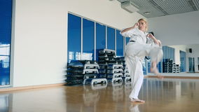 Au ralenti : la femme attirante démontre un tour de karaté dans le gymnase banque de vidéos