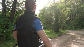 Au ralenti suivez du jeune homme handicapé d'étudiant dans un fauteuil roulant en observant la nature autour de lui, avec la fusé banque de vidéos