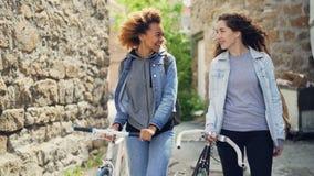 Au ralenti touristes de filles heureuses de Caucasien et d'Afro-américain riant et marchant avec des bicyclettes le long de rue a banque de vidéos