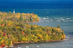 Au Sable Point Lighthouse. The Au Sable Light Station, surrounded by colorful fall foliage, stands on the Lake Superior shore of Michigan's Upper Peninsula at Royalty Free Stock Photos