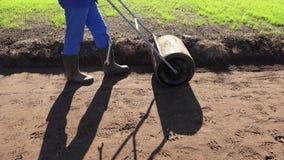 Au sol compact de sol d'homme de jardinier avec le rouleau après ensemencement de la pelouse Tir tenu dans la main banque de vidéos