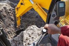 Au sol de creusement de trou d'excavatrice images stock