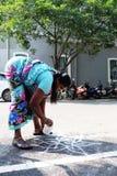 Au sujet du trottoir d'Inde dessinant Kolam/Rangoli sur le plancher Photo stock