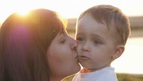 Au temps de soirée avant le coucher du soleil, le sentiment de bébé heureux et les sourires avec sa mère dans le jardin Photographie stock