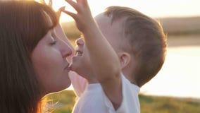 Au temps de soirée avant le coucher du soleil, le sentiment de bébé heureux et les sourires avec sa mère dans le jardin Image libre de droits