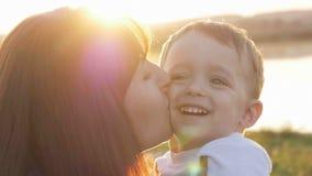 Au temps de soirée avant le coucher du soleil, le sentiment de bébé heureux et les sourires avec sa mère dans le jardin Photo stock