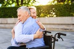 Au vieil homme qui s'assied en parc sur un fauteuil roulant est venu son fils Il étreint le vieil homme Images stock