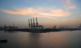 Aube au-dessus d'un port fonctionnant de cargaison photographie stock