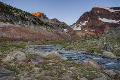 Aube au-dessus de chaîne de cascade et de lac alpin Image stock