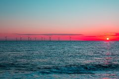 Aube cramoisie Turbines de ferme de vent de reflux d'énergie propre aux sunris Image libre de droits