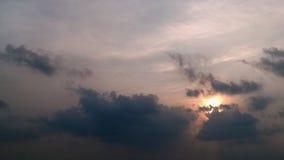 Aube dans le ciel : le disque du soleil est une couleur orange tendre parmi les cumulus gris-foncé sur un ciel bleu-clair Photographie stock libre de droits