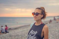 Aube de coucher du soleil Jeune femme se tenant sur les pierres arrondies d'un caillou La fille apprécie la plage peu commune, ca Photos stock