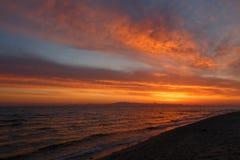 Aube orange de ressort sur le rivage de la mer calme pendant la marée Photo libre de droits