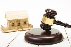 aubergine Закон Миниатюрный дом на деревянном столе и молотке суда стоковая фотография