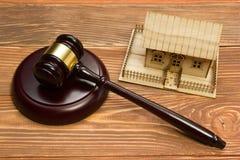 aubergine Закон Миниатюрный дом на деревянном столе и молотке суда стоковое изображение