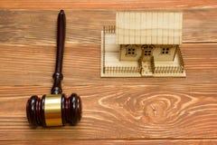 aubergine Закон Миниатюрный дом на деревянном столе и молотке суда стоковая фотография rf