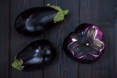Aubergine (aubergine) op donkere houten lijst Hoogste mening Verse ruwe landbouwbedrijfgroenten - oogst van de tuin in platteland Royalty-vrije Stock Afbeeldingen