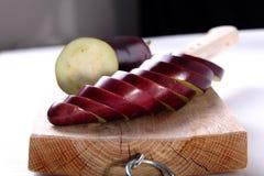 Aubergine coupée en tranches sur un coupeur en bois Photos libres de droits