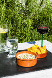 Aubergine dip in ceramic bowl with tortilla chips and iced water Royalty Free Stock Photo