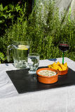 Aubergine dip in ceramic bowl with tortilla chips and iced water Stock Photo
