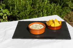 Aubergine dip in ceramic bowl with tortilla chips. Outdoors on s Stock Photo