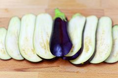 Aubergine or eggplant with slices on wooden background. Close up Stock Photos