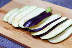 Aubergine or eggplant with slices on wooden background. Close up Royalty Free Stock Photos