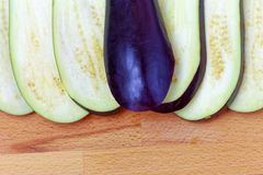 Aubergine or eggplant with slices on wooden background. Close up Stock Image
