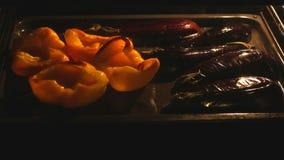 Aubergine en groene paprika het koken in oven stock footage