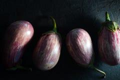 Aubergine im Streifen mit Niederlassungen auf dunkelgrauer Tabellennahaufnahme Stockfotos