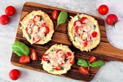 Aubergine minipizza's op een dienende raad tegen marmer Stock Fotografie