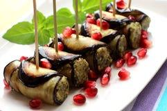 Aubergine rullar med muttrar Läcker startknapp av stekte aubergine med muttrar, örter och granatäpplefrö Royaltyfria Bilder