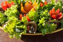 Aubergine rullar, och grönsallatsidor som dekoreras med blommor, klipper från körsbärsröda tomater på träbakgrundssidosikt Arkivfoto