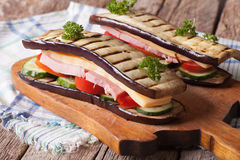 Aubergine sandwich with fresh vegetables, ham and cheese closeup Royalty Free Stock Photos