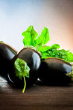 Aubergine and spinach on wood Stock Photo