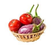 Auberginen und Tomaten im Korb lokalisiert auf Weiß Lizenzfreie Stockfotografie