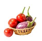Auberginen und Tomaten im Korb lokalisiert auf Weiß Stockbilder