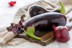 Aubergines и фиолетовый базилик на разделочной доске Стоковые Фото