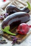 Aubergines и фиолетовый базилик на разделочной доске Стоковое Изображение