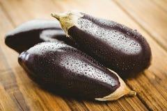 3 aubergines на деревянной доске Стоковые Фото