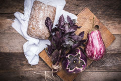 Aubergines, basil and bread on chopping board and wood Stock Images