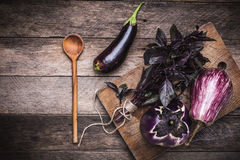Aubergines, basil and spoon on wooden table Stock Image
