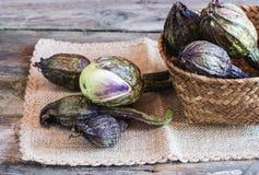 Aubergines de brinjal sur la serviette et le panier Image libre de droits